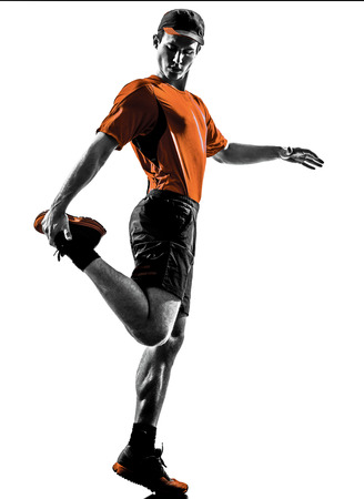 man isolated: one young man runner jogger stretching warming up in silhouette isolated on white background Stock Photo