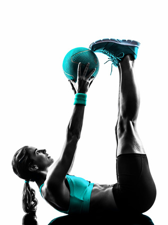 one caucasian woman exercising Medicine Ball  fitness in studio silhouette isolated on white background Imagens