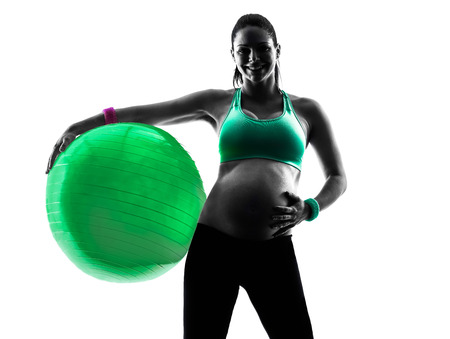 woman white background: one caucasian pregnant woman exercising fitness exercises  in silhouette studio isolated on white background