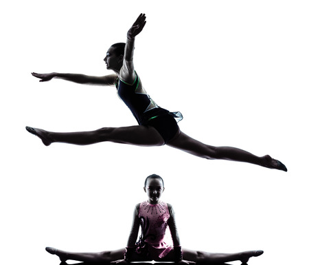 gymnastics silhouette: one caucasian woman teenager  and little girl child exercising Rhythmic Gymnastics in silhouette isolated on white background Stock Photo