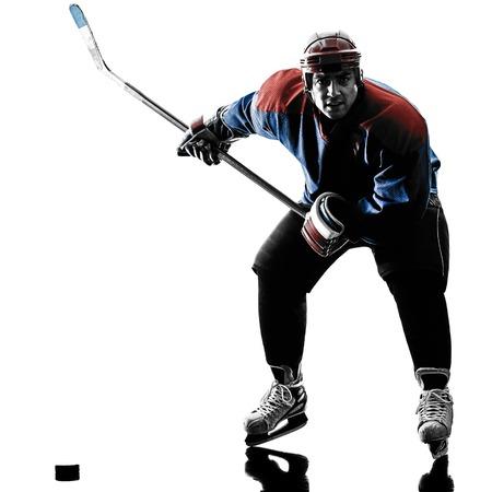 iluminado a contraluz: jugador de hockey sobre hielo de un hombre caucásico en el estudio de la silueta aislado en el fondo blanco