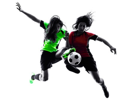 in action: two women playing soccer players in silhouette isolated on white background