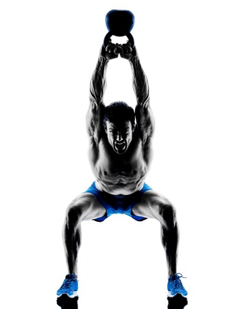 one caucasian man exercising fitness Kettle Bell weights exercises in studio silhouette isolated on white background