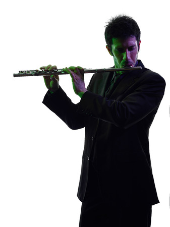 transverse: one caucasian man transverse flute player in studio silhouette isolated on white background