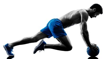 topless: one caucasian man exercising fitness plank position exercises Medicine Ball in studio silhouette isolated on white background Stock Photo