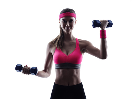 Weights: one woman fitness weights training  exercises  in studio silhouette isolated on white background