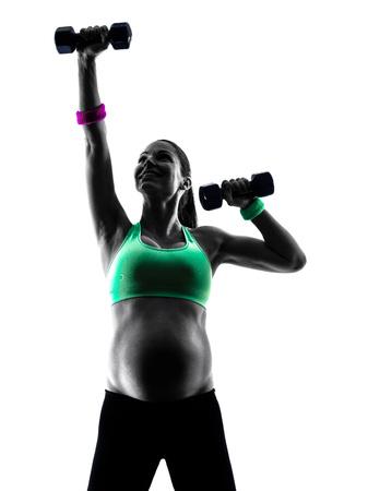 pesas: una mujer embarazada que ejercita ejercicios de fitness caucásico en estudio de la silueta aislado en el fondo blanco