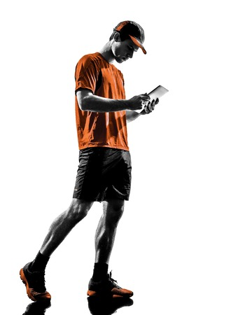 men running: one young man runner jogger using digital tablets ipad in silhouette isolated on white background