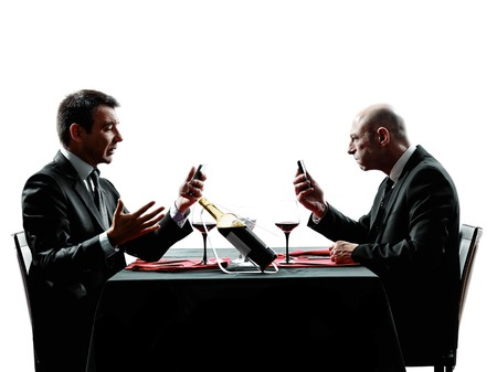 business dinner: two businessmen dinning using smartphones in silhouettes on white background