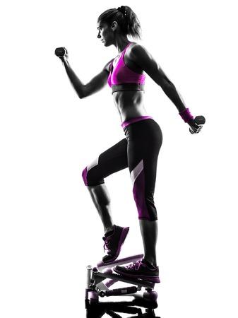 una mujer caucásica de pasos ejercicio con pesas de fitness en el estudio de la silueta aislado en el fondo blanco