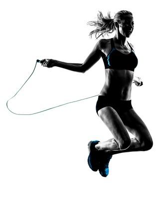 personas saltando: una mujer caucásica ejercicios de salto de cuerda en el estudio de silueta aislados sobre fondo blanco