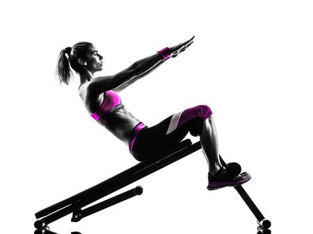 mujeres fitness: una mujer caucásica que ejercita en estudio de la silueta aislado en el fondo blanco Foto de archivo