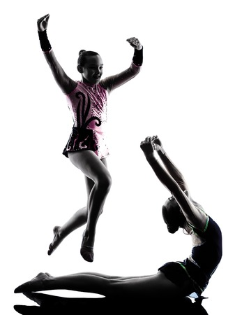 one teenager: one caucasian woman teenager  and little girl child exercising Rhythmic Gymnastics in silhouette isolated on white background Stock Photo