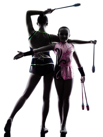 one teenager: one caucasian woman teenager and little girl child exercising Rhythmic Gymnastics in silhouette isolated on white background