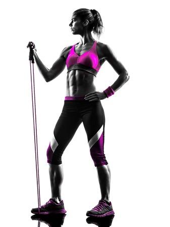 siluetas de mujeres: una mujer caucásica bandas de resistencia de fitness ejercicio en el estudio de silueta aislados sobre fondo blanco
