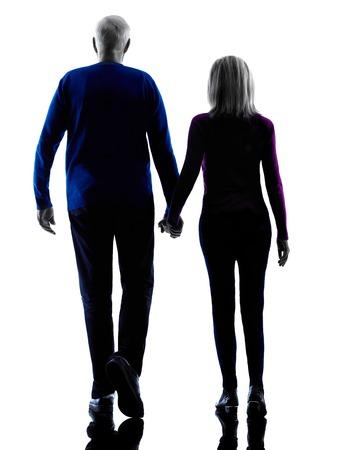 iluminado a contraluz: un caucásico pareja vista trasera altos caminar silueta en estudio de la silueta aislado en el fondo blanco Foto de archivo