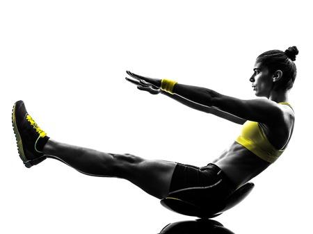 iluminado a contraluz: un caucásico mujer el ejercicio de abdominales de fitness en el estudio de la silueta aislado en el fondo blanco Foto de archivo