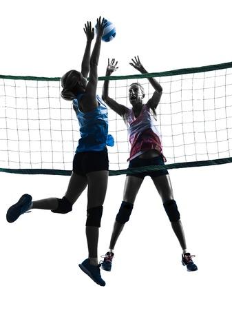 voleibol: dos mujeres caucásicas de voleibol en el estudio de la silueta aislado en el fondo blanco