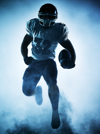jugando futbol: retrato jugador de fútbol americano en la sombra de la silueta en el fondo blanco Foto de archivo