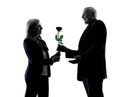 lovers: one caucasian couple senior lovers flower rose silhouette  in silhouette studio isolated on white background Stock Photo