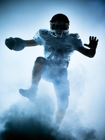 jugando futbol: retrato jugador de f�tbol americano en la sombra de la silueta en el fondo blanco Foto de archivo