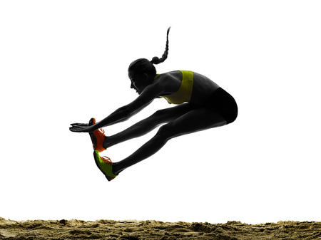 atleta: una mujer praticing silueta de salto de longitud en el estudio de la silueta aislado en el fondo blanco Foto de archivo