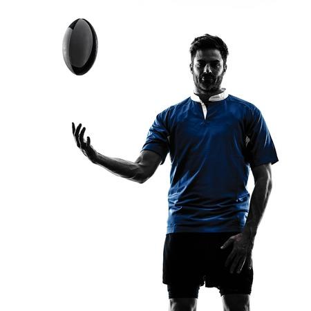 iluminado a contraluz: un caucásico hombre jugador de rugby en el estudio de la silueta aislado en el fondo blanco