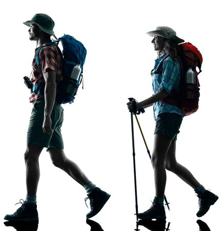 people shadow: one caucasian couple trekker trekking walking nature in silhouette isolated on white background Stock Photo