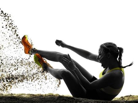 一人の女性捉え走り幅跳びシルエット スタジオ シルエットの白い背景で隔離の 写真素材