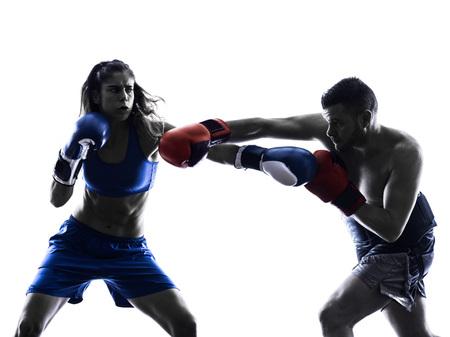 iluminado a contraluz: una mujer boxeador boxeo un hombre kickboxing en silueta aislados sobre fondo blanco Foto de archivo