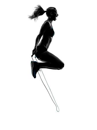 iluminado a contraluz: una mujer caucásica ejercicios de salto de cuerda en el estudio de silueta aislados sobre fondo blanco