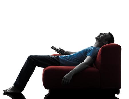 gente durmiendo: un hombre caucásico sofá sofá-cama mando a distancia viendo la televisión en la silueta aislado en el fondo blanco