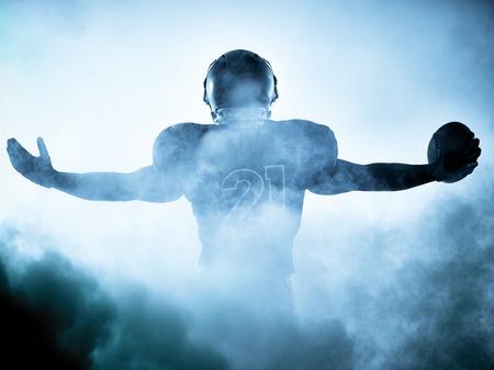jugadores de futbol: retrato jugador de f�tbol americano en la sombra de la silueta en el fondo blanco Foto de archivo