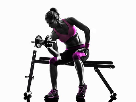pesas: una mujer caucásica edificio pesos que ejercen el cuerpo físico en la silueta del estudio aislada en el fondo blanco