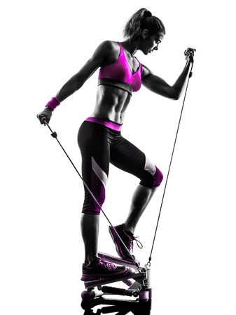 band: one caucasian woman exercising stepper resistance bands fitness in studio silhouette isolated on white background