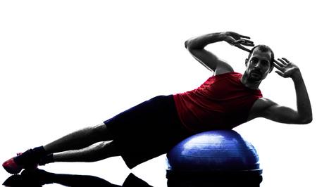 iluminado a contraluz: un hombre entrenador equilibrio bosu fitness ejercicio en silueta aislados sobre fondo blanco Foto de archivo