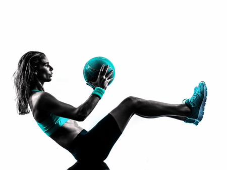 muscular woman: one caucasian woman exercising Medicine Ball  fitness in studio silhouette isolated on white background Stock Photo