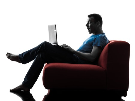 sofa: one caucasian man sofa couch computer computing laptop surprised in silhouette isolated on white background