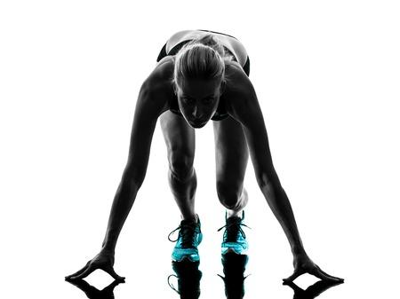 ein kaukasisch Frau running Jogger Joggen auf Startblöcke im Studio Silhouette auf weißem Hintergrund isoliert