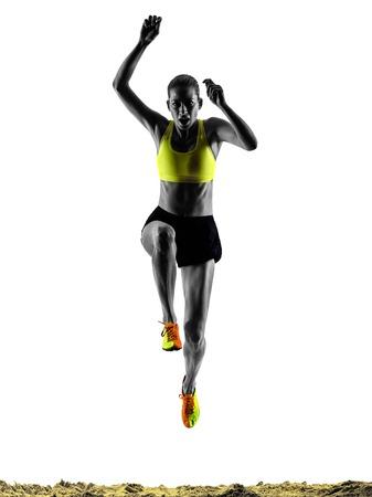 salto largo: una mujer praticing silueta de salto de longitud en el estudio de la silueta aislado en el fondo blanco Foto de archivo