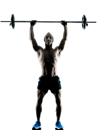 body building: one caucasian man exercising fitness body building exercises in studio in silhouette isolated