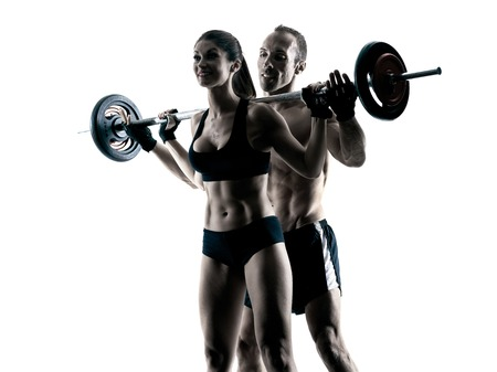 one caucasian couple exercising fitness body building exercises in studio in silhouette isolated 版權商用圖片