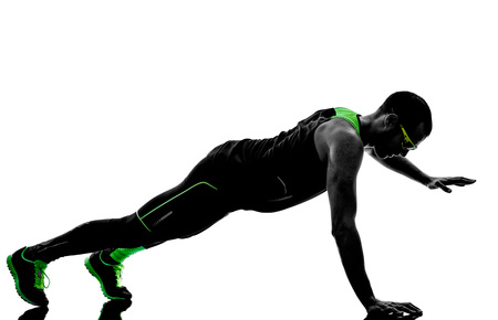 ups: one man exercising push ups fitness  in silhouette isolated on white background Stock Photo