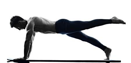 ein kaukasisch Mann Ausübung Pilates-Übungen Fitness in der Silhouette auf weißen Hintergrund isoliert