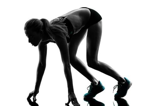 starting blocks: one caucasian woman runner running jogger jogging on starting blocks  in studio silhouette isolated on white background