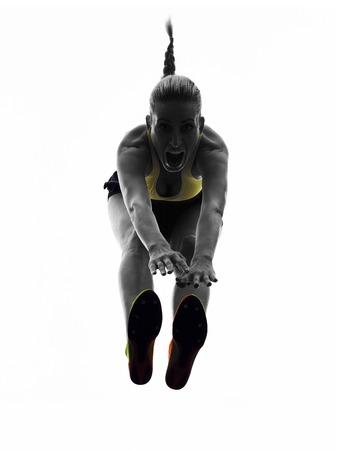 salto de longitud: una mujer praticing silueta de salto de longitud en el estudio de la silueta aislado en el fondo blanco Foto de archivo