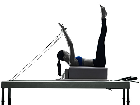 one caucasian woman exercising pilates reformer exercises fitness in silhouette isolated on white backgound 免版税图像