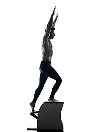 one caucasian man exercising pilates chair exercises fitness in silhouette isolated on white backgound Archivio Fotografico