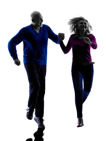 men running: one caucasian couple senior silhouette  in silhouette studio isolated on white background Stock Photo
