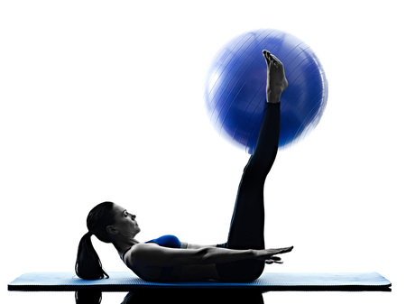 ball isolated: one caucasian woman exercising pilates ball exercises fitness in silhouette isolated on white backgound Stock Photo